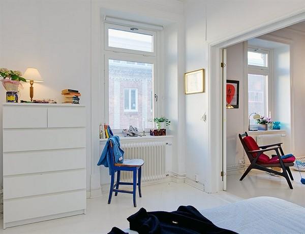 mėlyna kėdė, raudonas fotelis baltos sienos buto interjere