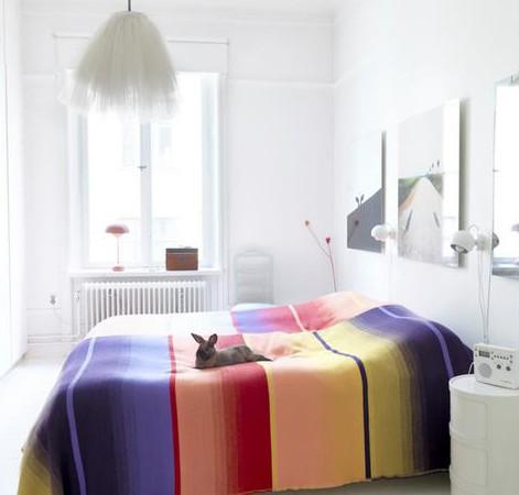 baltas miegamasis su spalvota antklode ant lovos