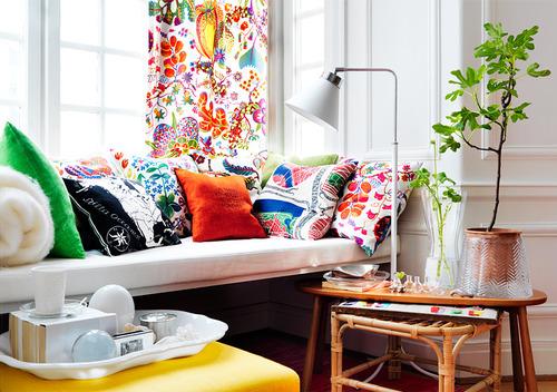 įvairių spalvų pagalvėlės, užuolaidos baltame kambaryje