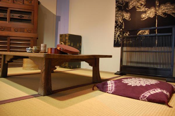 kambario interjeras, kilimas, pagalvėlė, stalas