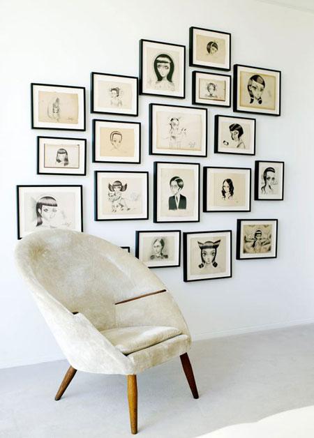 piešiniai juoduose rėmeliuose, fotelis kambaryje