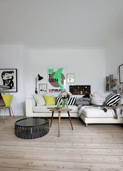 balta sofa, baltos sienos, paveikslai, medinis staliukas