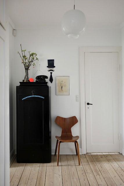 juoda spinta, medinė kėdė, baltos durys, siena