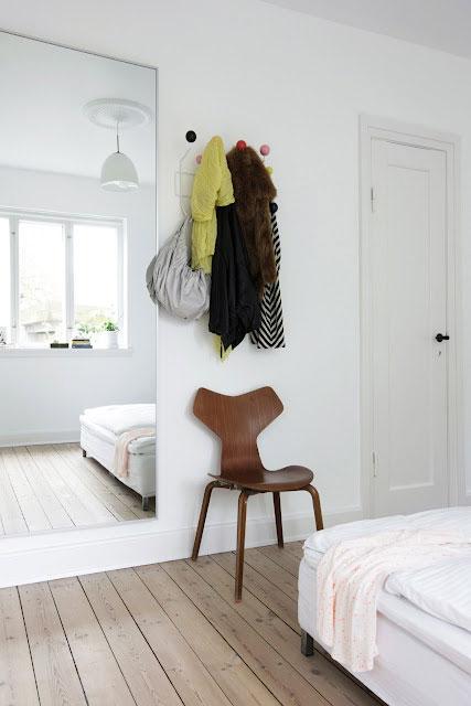 kėdė, rūbai ant pakabos, lova, veidrodis miegamąjame