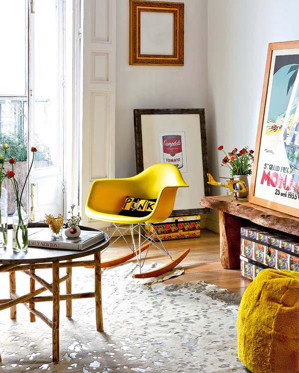 geltonas supuojantis fotelis, pufas, paveikslai svetainėje