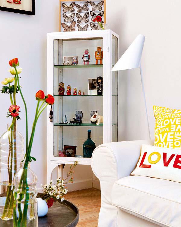 balta komoda su stiklinėmis lentynėlėmis, gėlės, sofa