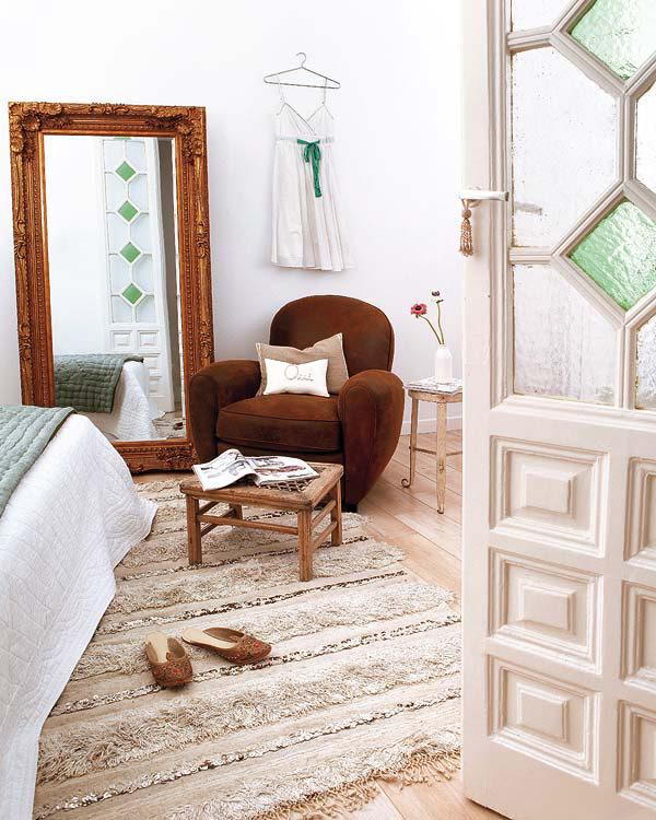 rudas minkštas fotelis,  didelis veidrodis ant grindų miegamąjame