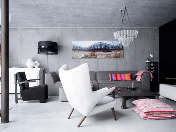 baltas fotelis, pilka sofa, betoninės sienos svetainėje
