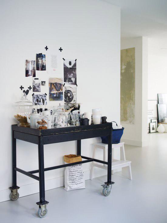 juodas stalas ant ratukų, apkrautas indais