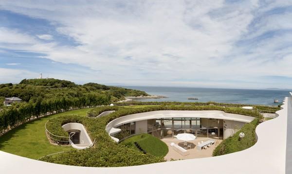 apvalių formų namas jūros pakrantėje