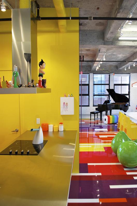 industrinis loftas, spalvotos grindys, geltona virtuvė, juodas fortepionas