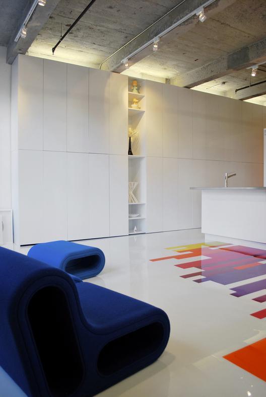 industrinis loftas, lentynėlė baltoje sienoje, mėlyna sofa
