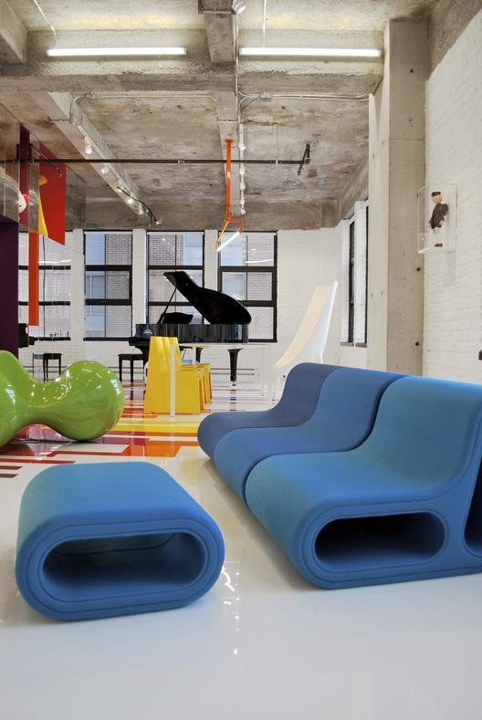 industrinis loftas, spalvotos grindys, juodas fortepionas, mėlyna sofa, geltonos kėdės