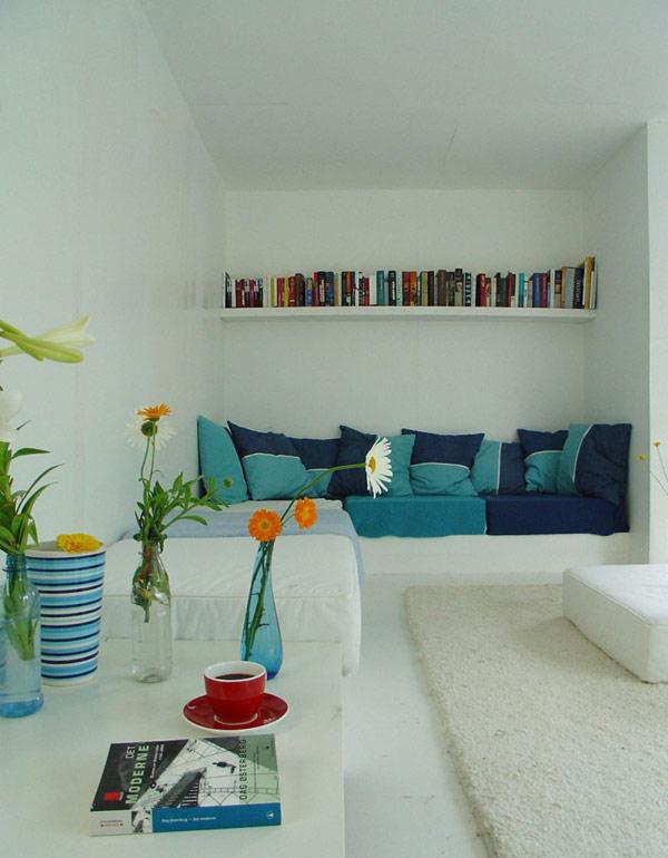 24 m2 namo interjeras, baltas svetainė, mėlymos pagalvėlės