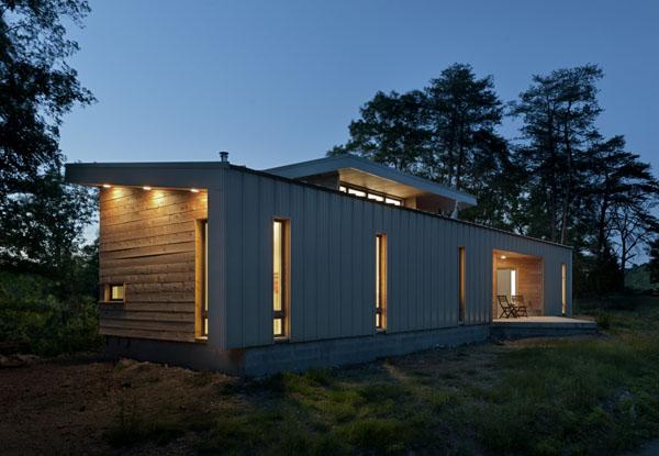 Ridgehouse namas vakare, siauri vertikalūs langai