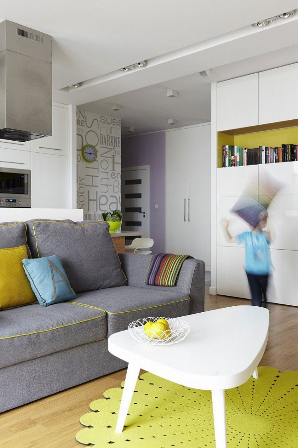 pilka sofa geltona pagalvele